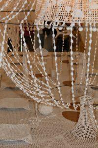 hæklet dug med forskellige genstande der tilhører bordet.